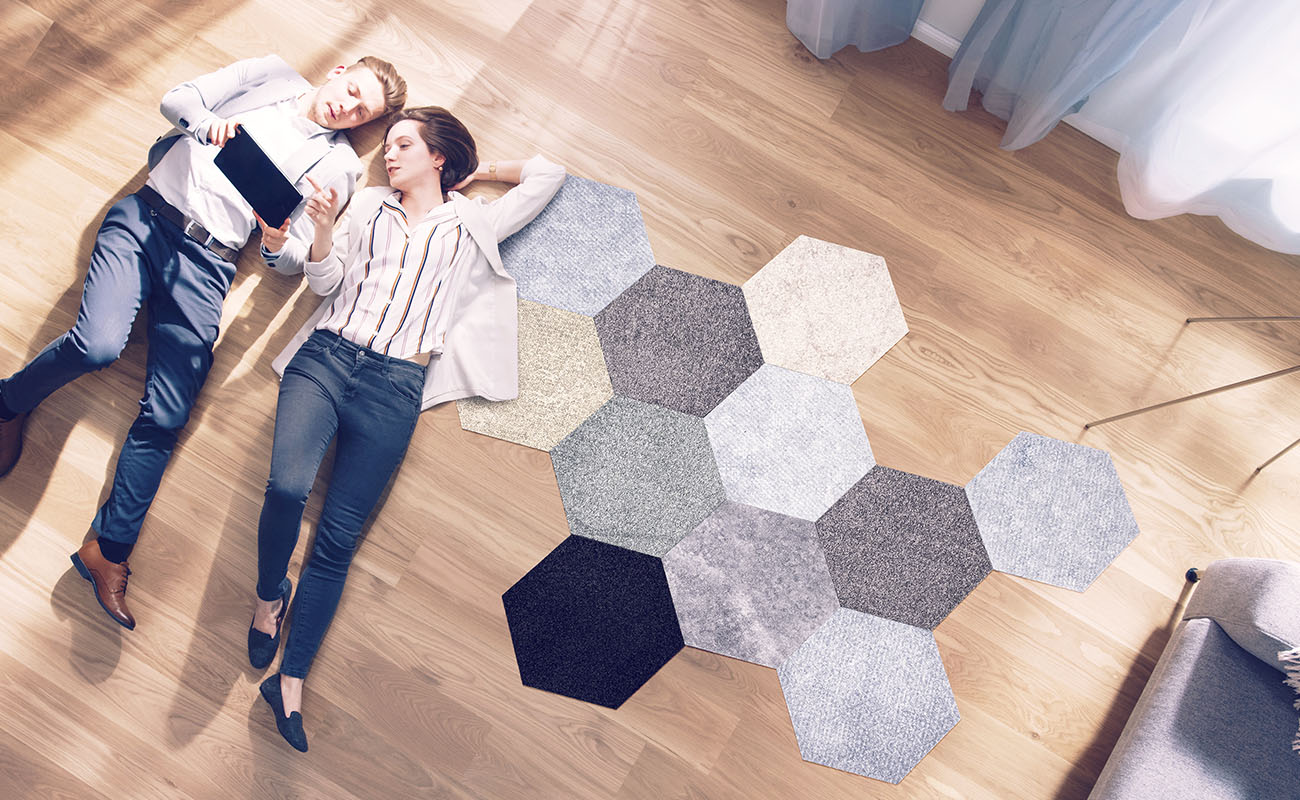 Couple on the floor with carpet tiles besides them